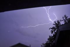 A cloudy gray night sky with a lightning bolt split into five streams.