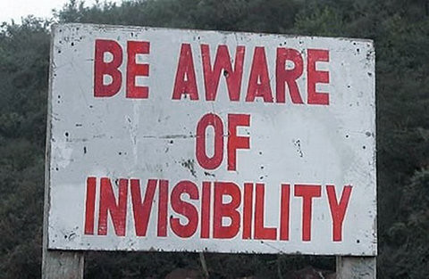 Red and white sign that reads BE AWARE OF INVISIBILITY