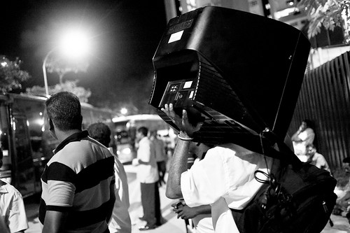 A migrant worker carrying a TV on his shoulders, waiting for his ride home.