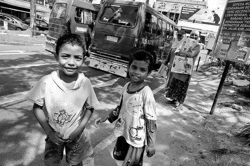 Kids selling newspapers at traffic junction in Batam
