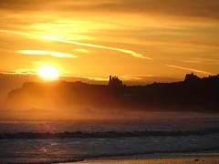 The sunrise starts (barronr) Tags: sea england sky orange cliff sun lighthouse beach abbey sunrise yorkshire northsea whitby groyne sandsend