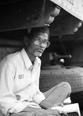 Mumbai, September 1999 (Riverman___) Tags: travel portrait blackandwhite india man blancoynegro film 50mm reading glasses md minolta 28mm 400 bombay hp5 mumbai ilford fp4 125 x700 f17 rokkor