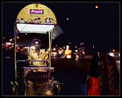 ice cream man and the girl in the red dress (PNike (Prashanth Naik..back after ages)) Tags: street india man girl yellow night dark 50mm nikon traffic streetphotography icecream roads citystreets hyder