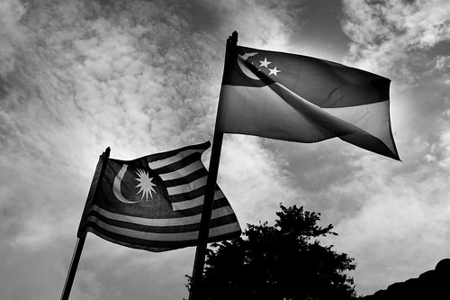 Singapore and Malaysia flags fly side by side over the Bukit Timah KTM railway station