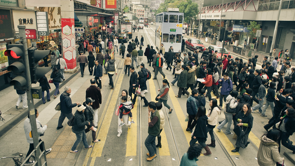 people of hong kong crossing the street in front of the tram