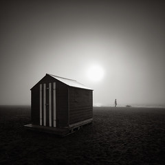 Early Morning Walk (Andy Brown (mrbuk1)) Tags: light sea sun beach silhouette sepia contrast square landscape blackwhite sand glow stripes shoreline devon beachhut toned stroll frontpage vignette dogwalking luminance teignmouth