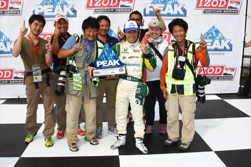 Takuma Sato celebrates with his entourage of photographers