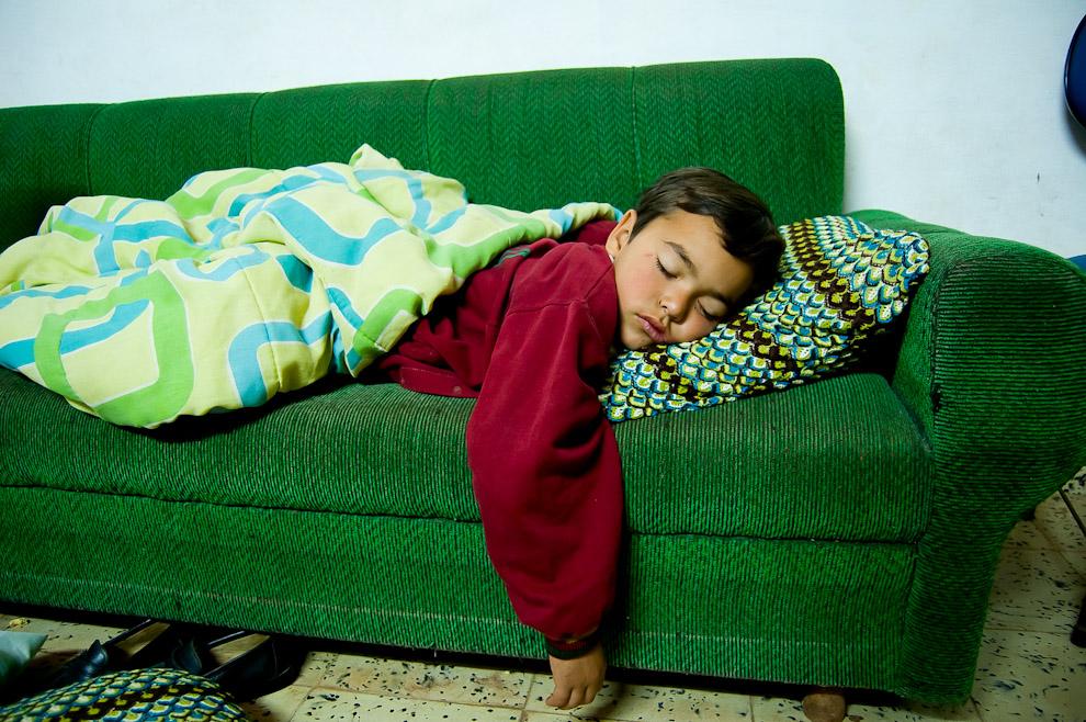 Un niño duerme profundamente en el sofá mientras se llevaba a cabo una fiesta de quince años en una casa del barrio Laguna Satí de Fernando de la Mora. (Elton Núñez)