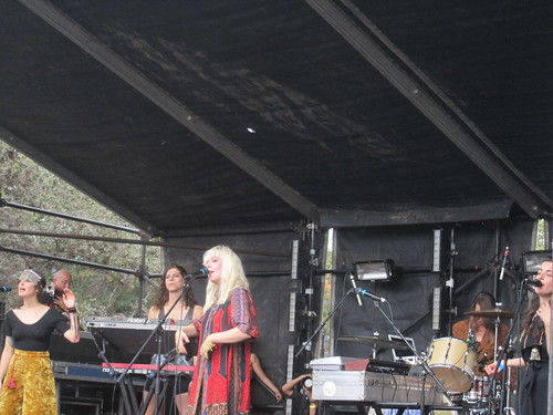 Austra, with platinum hair and a red frock, sings, while her band sings and plays behind her.