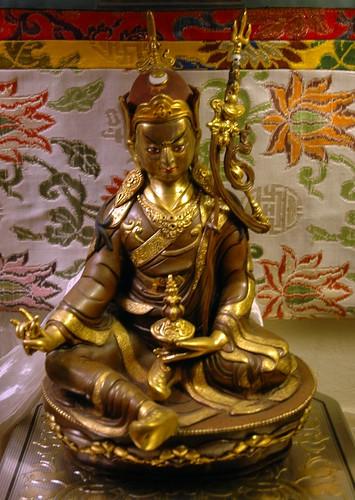 Statue of Padmasambhava, 8th century saint who brought Buddhism to Tibet, floral Tibetan style silks, khata (kata), ornate box, Seattle, Washington, USA by Wonderlane