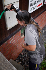 Cooling off with a hose at the Makkari camping ground, Makkari, Hokkaido, Japan