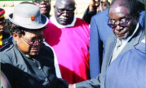President Mugabe consoles Vice-President Joice Mujuru during the burial of her husband, the late Retired General Solomon Mujuru, at the National Heroes' Acre in Harare yesterday, while Fr Fidelis Mukonori looks on. by Pan-African News Wire File Photos