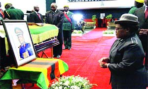FARE THEE WELL . . . Vice-President Joice Mujuru kneels before a portrait of her late husband Retired General Solomon Mujuru and the casket containing his body at Stodart Hall in Mbare yesterday morning. by Pan-African News Wire File Photos
