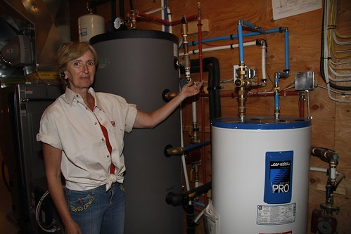 Shanon McNabb shows two water tanks used to manage hot water from solar thermal and geothermal systems