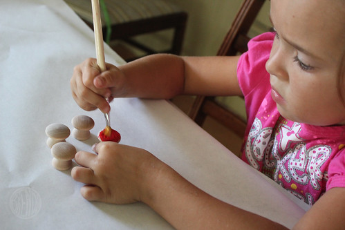 small child painting wooden knobs with red paint