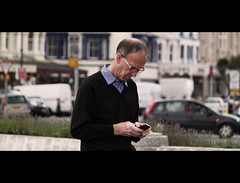 Catching up with Technology - Llandudno (AdamGalley) Tags: street wales photography focus emotion candid sharp streetphoto cinematic tones llandudno shocked galley kirkham candidphotography juststreet streetphotography adamgalley