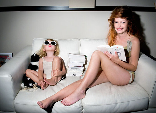 a young white woman and a white toddler sit on a couch wearing lingerie
