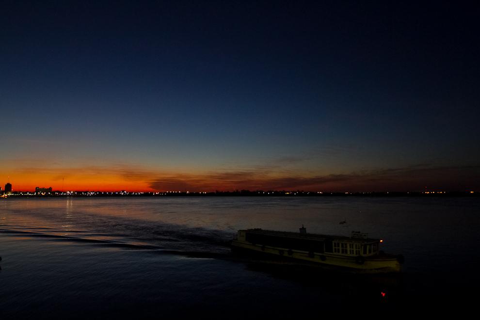 Un bote cruza desde la ciudad vecina de Formosa - Argentina a la Ciudad de Alberdi, mientras atardece en el horizonte. (Tetsu Espósito)