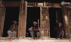 Afghan Mujahideen 1985 Nuristan (Afghan Pashtun) Tags: wood people afghanistan men clothing holding war asia gun asians pants rifle beards few doorway shirts jacket weapon blanket afghan males prominentpersons leader warriors facialhair posture everydayscenes fighters crouching patience squatting pathan outerwear pakhtun threepeople pashtun jehad centralasians pashton nuristanprovince nuristanis pakols