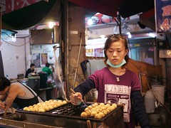 Rotating Balls at the Night Market (weizor) Tags: portrait food motion cute cooking girl night dessert awning lumix restaurant movement asia 6ws sixwordstory taiwan panasonic nightmarket pastries chiayi streetfood jiayi tw micro43 microfourthirds 20mmf17asph dmcg3