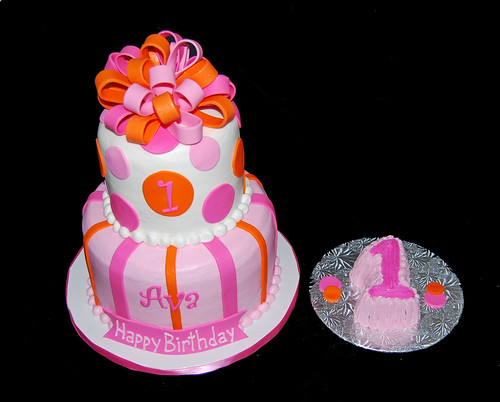 pink and orange 2 tier first birthday cake topped with a bow and smash cake