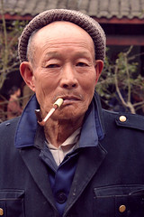 Smoking Old Man (Sunanda Chandry Koning) Tags: china old travel blue portrait man face hat digital canon vintage photography eos photo eyes asia 300d buttons cigarette pipe bald oldman smoking jacket cap chengdu aged knitted smoker sichuan wrinkles 2009 canoneos300d wrinkly woolenhat april2009