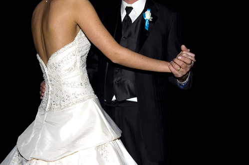 A bride and groom holding hands and dancing