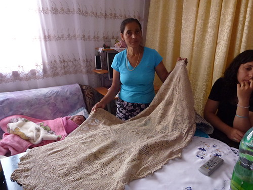 Fatima displaying a tentene tablecloth she made by hand using a pattern in a magazine.