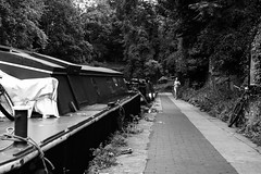jogger along regents canal (Paul Steptoe Riley) Tags: uk england urban blackandwhite woman london english public girl monochrome bicycle female britain candid documentary regentscanal british islington narrowboat jogger towpath canalboat