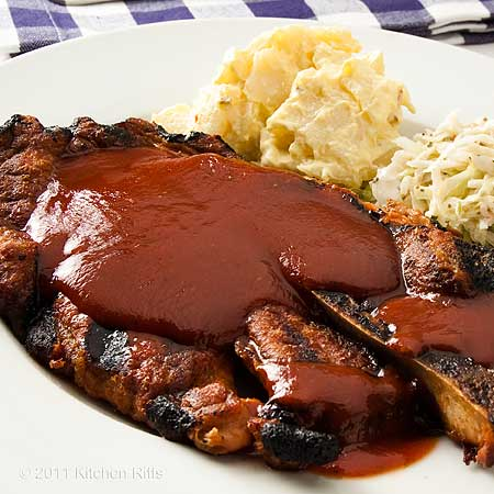 pork steak on plate covered with barbecue sauce
