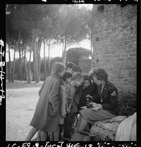 [Toni Frissell, sitting, holding camera on her lap, with several children standing around her, somewhere in Europe] (LOC) / The Library of Congress