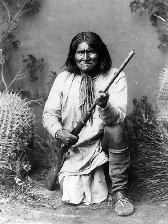 Photograph of geronimo kneeling with his rifle taken in 1887 by ben