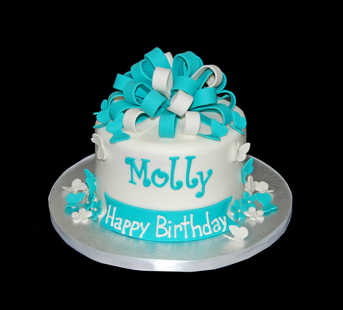 turquoise and whit birthday cake with butterflies and flowers topped with a bow