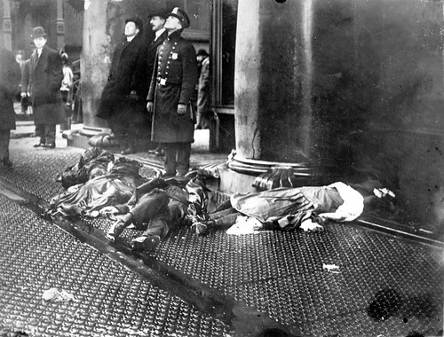 police-officer-with-bodies-of-Triangle-fire-victims-at-feet-looking-up-at-workers-poised-to-jump-from-the-upper-floors-of-the-burning-Asch-Building.jpg