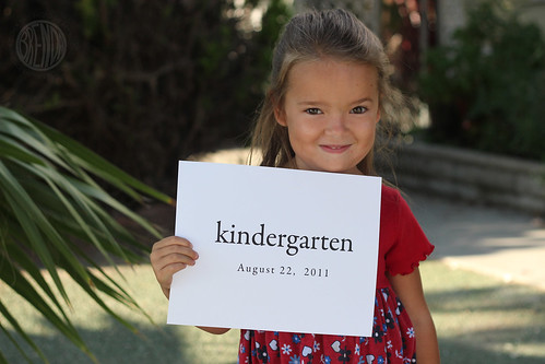 smiling girl holding up a piece of paper that says kindergarten