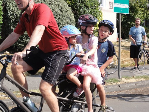3 kids and dad on bike. photo by Greg Raisman