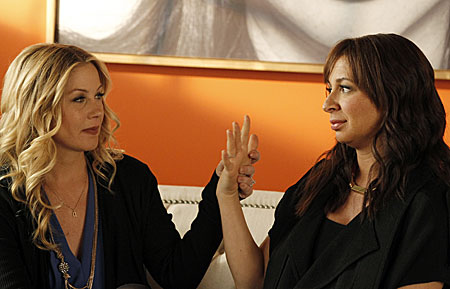 Maya Rudpolph and Christina Applegate sit on a couch touching hands