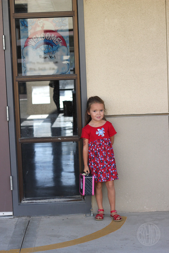 young girl in a red dress standing by her classroom door
