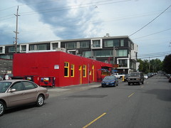A vividly red building with a modern condo behind it