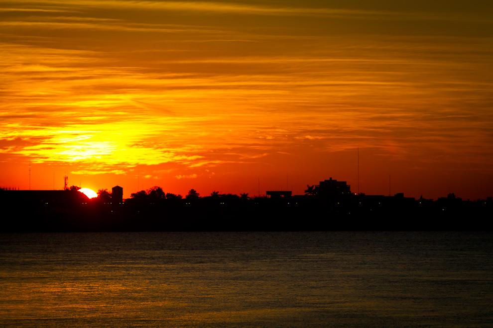 El sol se pierde en la ciudad vecina de Formosa - Argentina, desde el puerto en la Ciudad de Alberdi, Paraguay. (Tetsu Espósito)