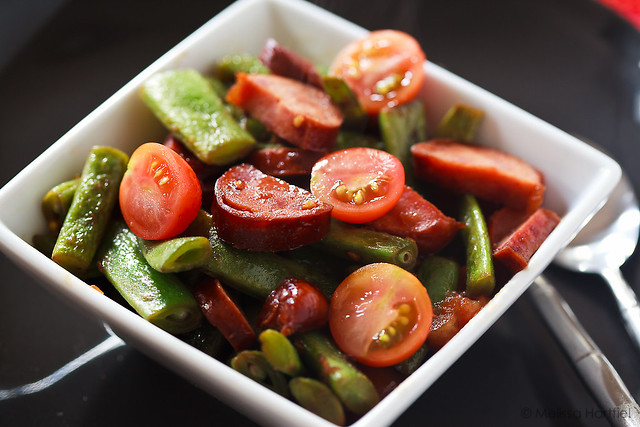 bowl of asian green beans with cherry tomatoes and sausage