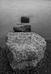 three in a row (B.Jansma) Tags: 2 bw white 3 black water photoshop canon silver three movement rocks long exposure belgium belgie stones smooth glad line le 25 simplicity sec zwart wit emptiness lightroom beweging zw rij drie stenen 500d eenheid leegte tellmewhatyouthink cs5 efex firstleever
