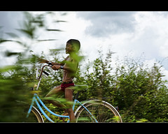 blue bicycle, red underwear and a very excited cambodian boy (explored) (PNike (Prashanth Naik)) Tags: street boy red sky green bike bicycle race nikon asia cambodia cycle siem reap siemreap panning d7000 pnike