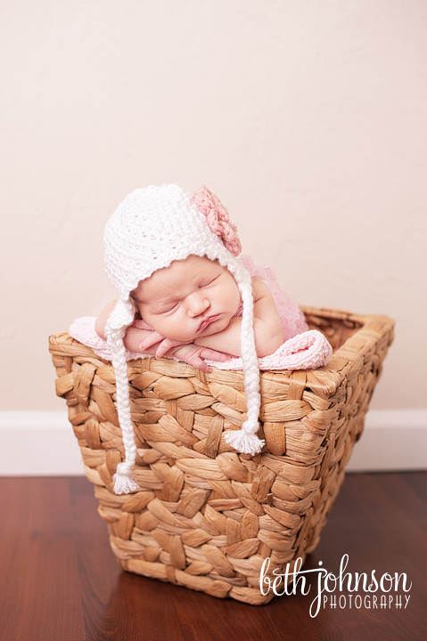 newborn baby girl in pink and white hat in basket in photography studio