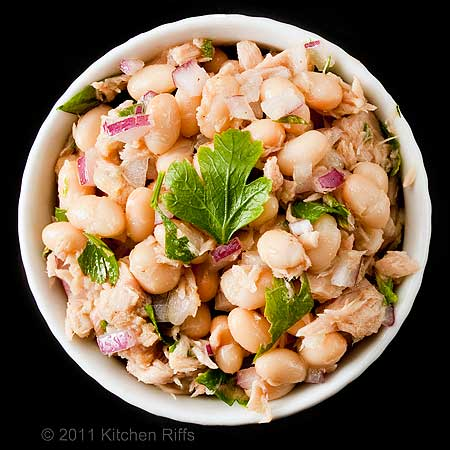 White Bean and Tuna Salad in ramekin on black background, overhead view
