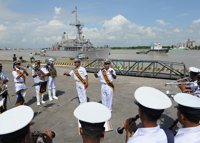 The Bangladesh Navy Band performs on the pier as USS Defender (MCM 2) maneuvers to arrive in Chittagong for exercise CARAT 2011