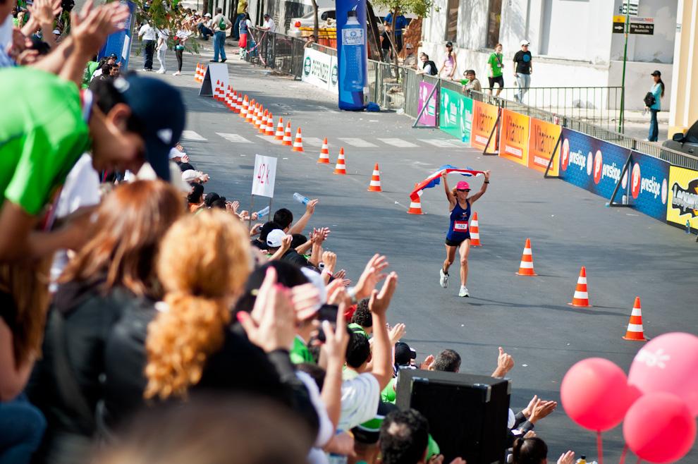 Nuestra compatriota Carmen Martínez Aguilera (162) festeja su triunfo a punto de concretarse, con la bandera paraguaya y ovacionada por el público, llega feliz a la meta completando su carrera en 2:55:11. Tiempo que la coloca en segunda posición en la categoría 42km. (Elton Núñez)