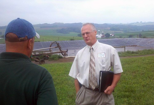 Lambert Rosenbaum, USDA Rural Development Area Director (right) discusses the newly installed anaerobic methane digester at Pennwood Farms in Somerset County, Pa. with Merv Yoder of RCM Digesters, the installer. The digester is currently producing more than enough energy to operate the farm.
