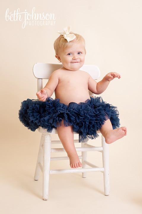 baby girl in navy pettiskirt in studio