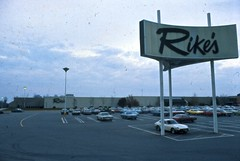 Rike's - Kettering, OH. (Wires In The Walls) Tags: ohio cars parkinglot slide vehicles departmentstore signage scanned disappeared kettering bygone rikes